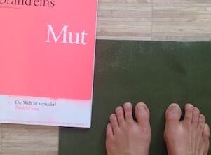 Auf diesem Bild steht Eva auf einer Yogamatte und Mut liegt neben ihr