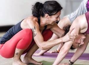 Auf diesem Bild ist Yogalehrerin Andrea, die einer Yogaschülerin im herabschauenden Hund, einer klassischen Yoga Übung, hilft.