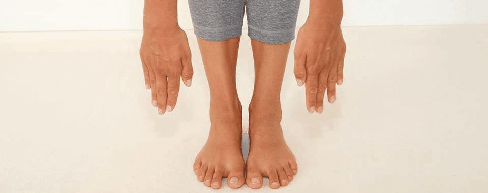 Yoga für Anfänger: ein Yogaschüler versucht in einer klassischen Yoga Haltung mit den Händen die Boden zu berühren.