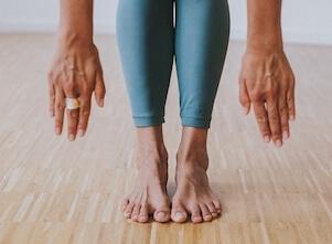 Yoga Lehrerin Eva steht in Uttanasana, einer Yoga Haltung, die man im Yoga Grundkurs lernt.