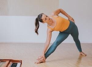 Yoga Lehrerin Eva steht in Trikonasana, einer Yoga Haltung, die man im Yoga Grundkurs lernt.