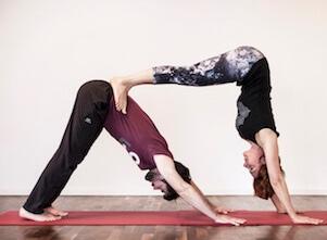 Partner-Yoga: Yogalehrerin Simone und Partner im Herabschauenden Hund in unserem Yoga Studio in Stuttgart West.