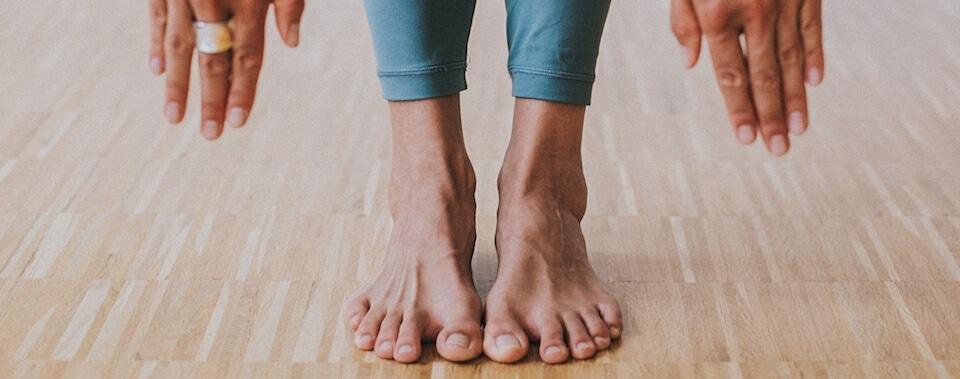 Yoga für Anfänger: ein Yogaschüler, der neu im Yoga ist, versucht in einer klassischen Yoga Haltung mit den Händen die Boden zu berühren.